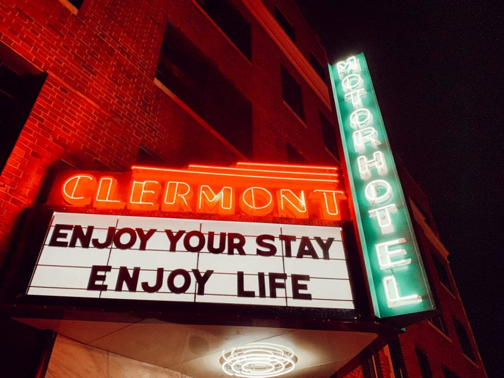 """Enjoy Your Stay, Enjoy Your Life"" neon marquee outside Hotel Clermont Atlanta"