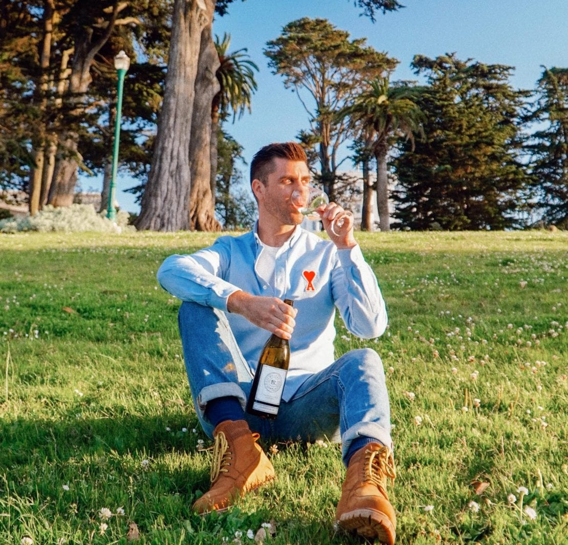 Kyle Legg, The Cosmopolitan Man, sipping Priest Ranch wine in San Francisco's Alamo Square Park.